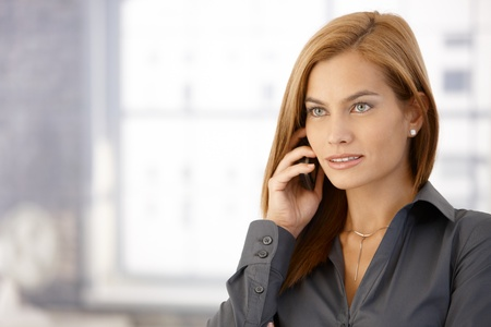 Portrait of young businesswoman concentrating on mobile phone call. photo
