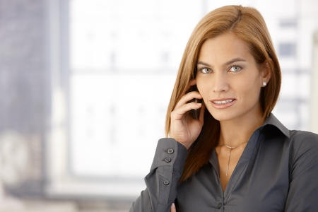 Businesswoman using cellphone, looking at camera, smiling. photo
