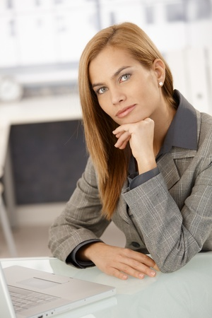 Portrait of smart businesswoman sitting at desk with laptop computer, thinking, looking at camera. Stock Photo - 8585526