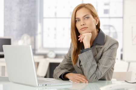 Portrait of determined businesswoman sitting at desk in office, looking at camera. Stock Photo - 8586842