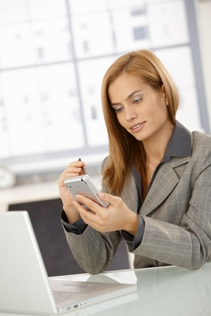Businesswoman using smartphone at office desk, smiling. photo