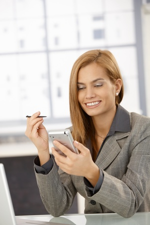Cheerful businesswoman using PDA in office, smiling. photo