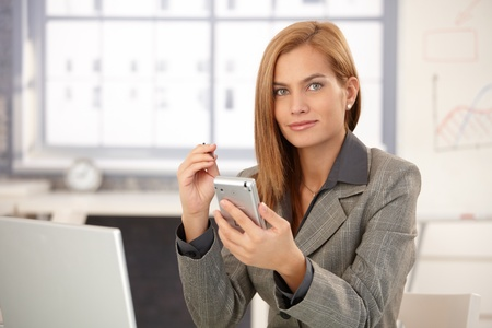 Portrait of businesswoman sitting in office, using PDA, smiling confidently. photo