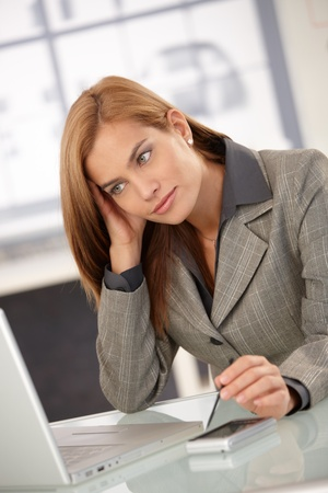 Young businesswoman sitting at desk, working on laptop computer, looking at screen, thinking. Stock Photo - 8587037