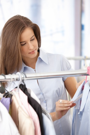 Smiling young woman shopping clothes, checking price tag on shirt. Stock Photo - 8604180