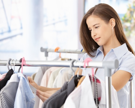 Pretty woman shopping clothes, looking at shirt price tag, smiling. Stock Photo - 8604018