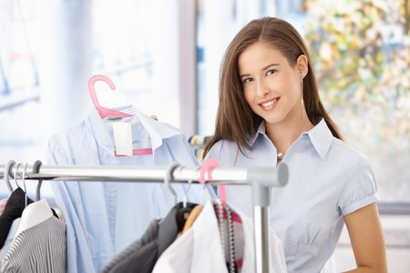 Happy woman shopping, holding shirt in clothes store, smiling at camera. Stock Photo - 8604230