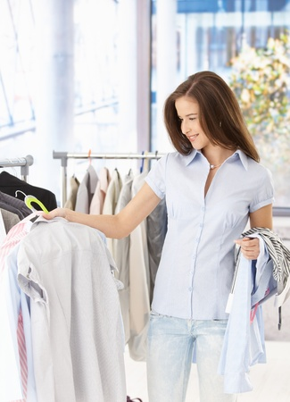 Pretty woman purchasing clothes in shop, smiling. Stock Photo - 8604154