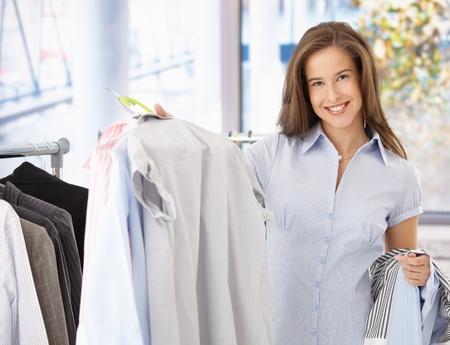 Feliz femenino cliente en la tienda de ropa, celebración de camisa, sonriendo a la cámara. Foto de archivo