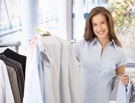 Happy female customer in clothes shop, holding shirt, smiling at camera. photo