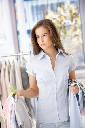 Smiling woman doing shopping, holding clothes, standing in store. Stock Photo - 8604237