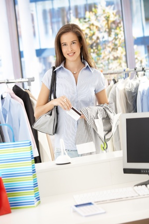 Happy woman paying her shopping with credit card in clothes store, looking at camera, smiling. photo