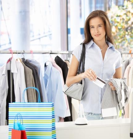 tarjeta de credito: Mujer de pie en la tienda de ropa, pagar con tarjeta de cr�dito, sonriendo a la c�mara.