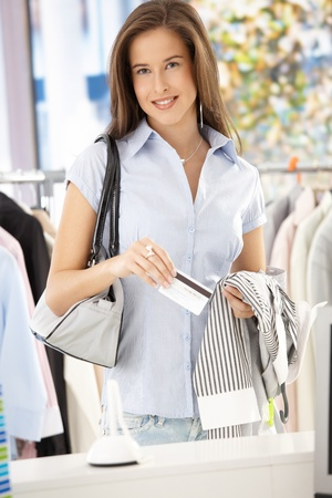 clothes store: Attractive woman purchasing shirt in clothes store with credit card, smiling at camera.