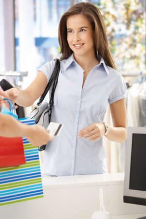 Woman purchasing clothes in shop, getting back credit card, smiling at shop assistant. Stock Photo - 8604235