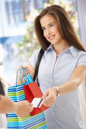 tarjeta de credito: Sonriente mujer despu�s de la compra, teniendo bolsas de compra y la tarjeta de cr�dito. Foto de archivo