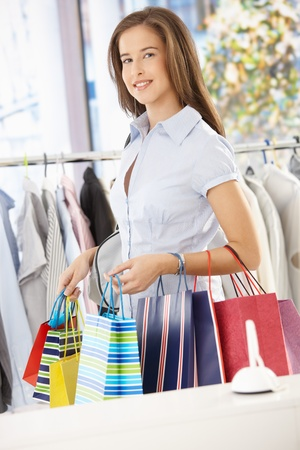 Happy woman leaving clothes shop with shopping bags, smiling at camera. Stock Photo - 8604205