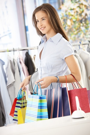 good mood: Portrait of shopping girl standing in clothes store, holding shopping bags.