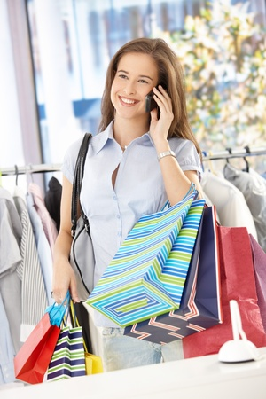 Female customer standing in clothes store, holding shopping bags, speaking on mobile phone, smiling happily. Stock Photo - 8604211
