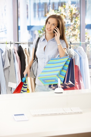 Woman standing in clothes shop, holding shopping bags, speaking on mobile phone, smiling. Stock Photo - 8604139