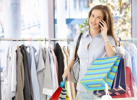 Woman on mobile phone call standing in clothes shop, holding shopping bags, smiling.