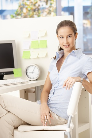 Portrait of pretty office girl sitting at desk, looking at camera. photo
