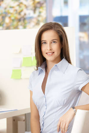 Portrait of attractive office worker girl smiling at camera. photo