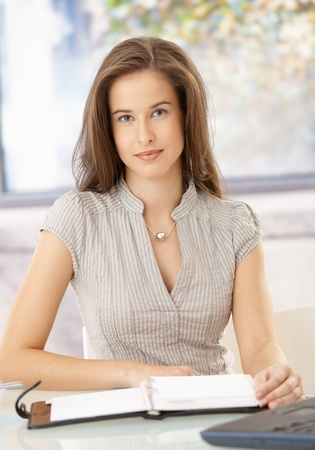 Portrait of businesswoman sitting at desk with calendar, looking at camera. Stock Photo - 8604157