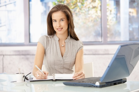 Smiling businesswoman sitting at desk in office, writing into personal organizer, looking at camera. photo