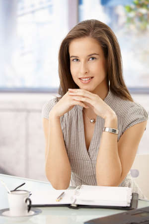 Businesswoman portrait in office, sitting at desk with organizer and coffee cup, smiling at camera. Stock Photo - 8604134