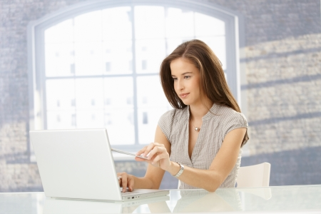 Woman sitting at table using laptop computer, pointing at screen, holding pen. Stock Photo - 8604019