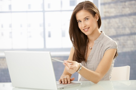 Cheerful young woman pointing at screen while reading on laptop computer, smiling at camera. Stock Photo - 8604001