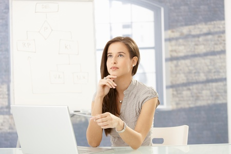 Businesswoman at work, looking up, pointing pen at screen, concentrating. Stock Photo - 8603991