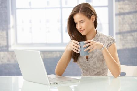 tea light: Beautiful smiling businesswoman at work looking at laptop computer screen, having tea. Stock Photo