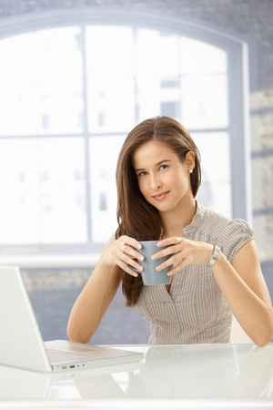 Portrait of businesswoman having coffee, sitting at table with laptop computer, smiling at camera. Stock Photo - 8604031
