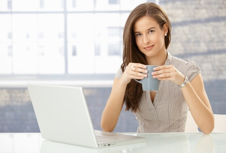 Portrait of smiling woman with laptop computer, holding coffee mug, looking at camera happily. Stock Photo - 8603989