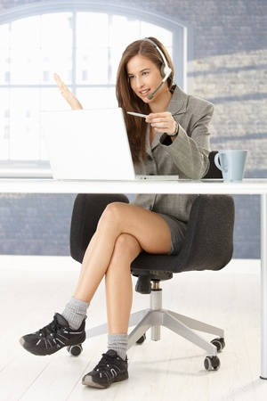 Funny portrait of call center operator girl working at desk, sitting in smart top but in comfortable shoes under table. Stock Photo - 8604206