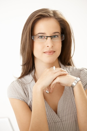 satisfied: Portrait of young attractive woman wearing glasses, looking at camera.