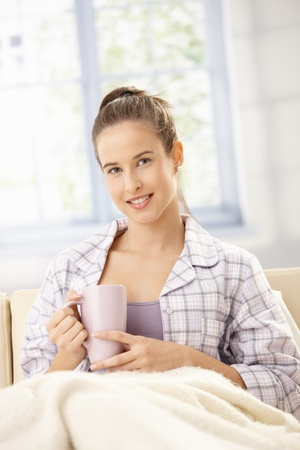 Happy woman in pyjama having morning coffee on couch, smiling. photo
