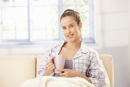 Attractive woman in pyjama drinking morning coffee in bright living room. photo