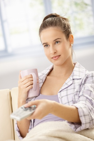 Pretty woman in pyjama sitting on couch with coffee mug, watching television in morning, changing channel with remote control. photo