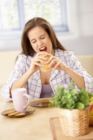 hambriento: Mujer hambrienta en pijama morder en sandwich en mesa del desayuno en casa.