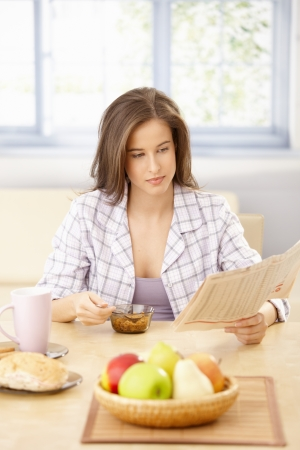 nighty: Portrait of young woman reading papers at breakfast table, having cereal.