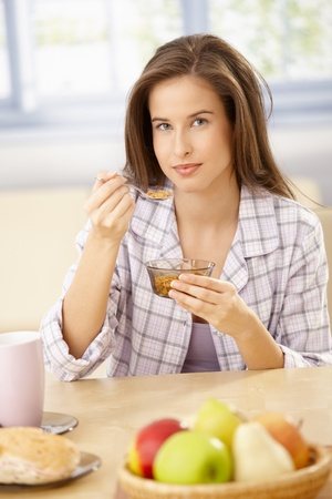 Smiling woman in pyjama sitting at kitchen table having cereal for breakfast. photo