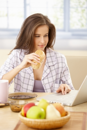Portrait of young woman using laptop computer at breakfast table, holding sandwich. photo