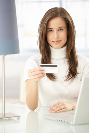 Portrait of pretty woman online shopping, using laptop computer and credit card. Stock Photo - 8604056