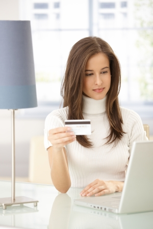 purchasing: Attractive woman doing electronic shopping online with credit card.