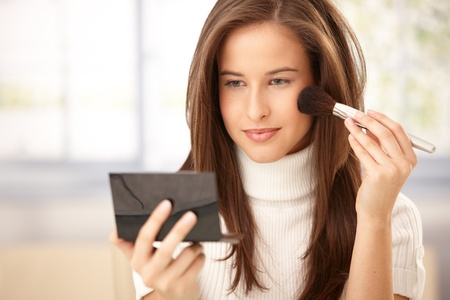checking in: Attractive woman applying makeup with brush, checking in pocket mirror, smiling. Stock Photo