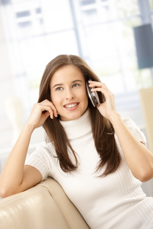 Happy woman on call, using mobile phone, sitting on sofa at home, smiling. Stock Photo - 8604124