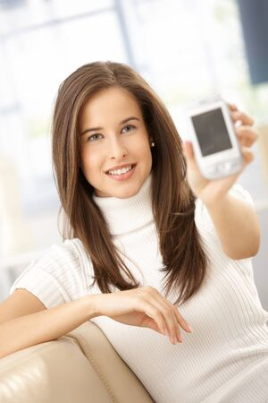 Smiling woman showing mobile phone, holding up to camera, smiling. photo